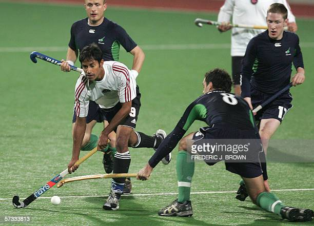 Canada's Ken Pereira dribbles past Ireland's Graham Shaw and Stephen Butler as Abour looks on during a Hockey World Cup Qualifier Pool A match 13...