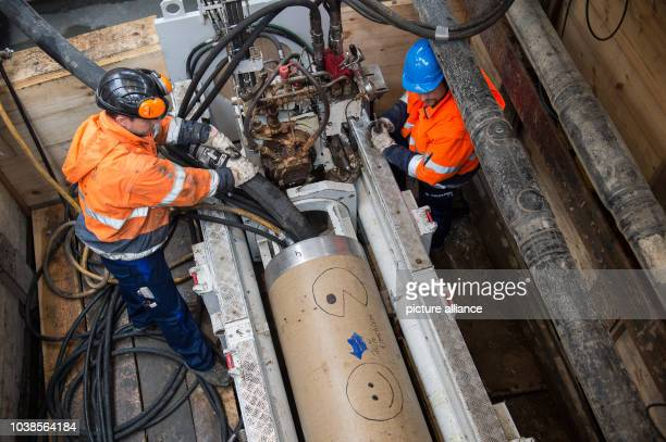 Channel diggers employed by the construction firm Frisch and Faust replace water pipes using a hydraulic machine produced by the manufacturer Pipe...