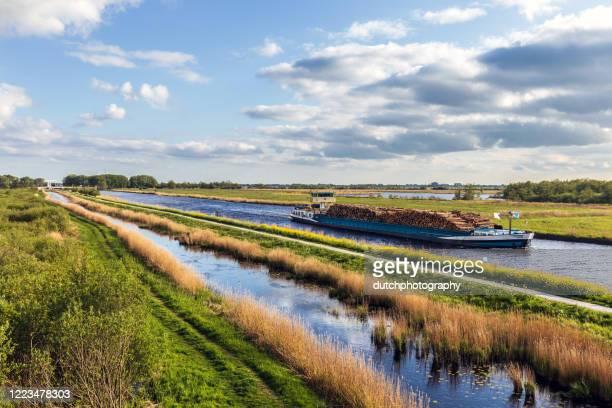 kanaal met vrachtschip met hout - geografische locatie stockfoto's en -beelden