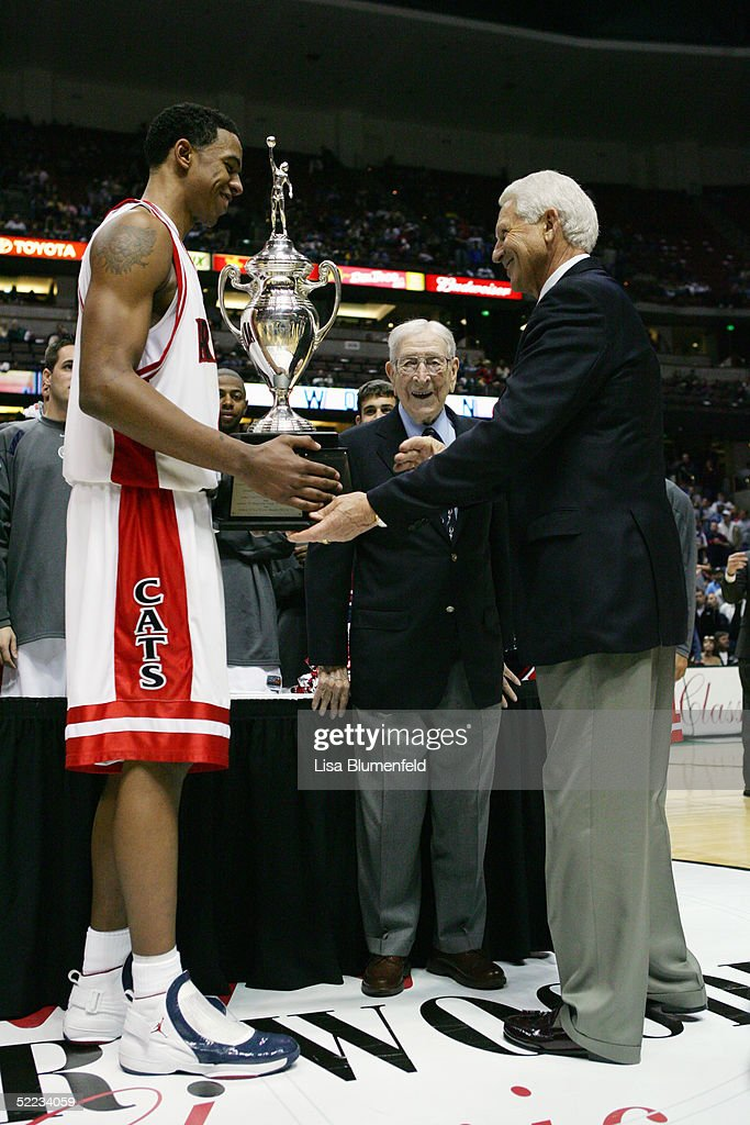 Channing Frye #45 and head coach Lute Olson of the Arizona Wildcats handle the John Wooden championship trophy as John Wooden (C) looks on after defeating the Mississippi State Bulldogs on December 5, 2004 at The Arrowhead Pond in Anaheim, California. The Wildcats won 68-64.