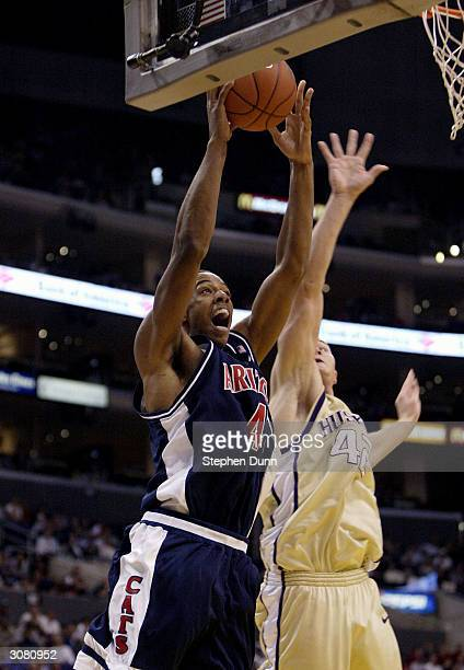 Channing Fyre of the Arizona Wildcats goes in for a slam dunk past Mike Jensen of the Washington Huskies during the semifinals of the 2004 Pacific...