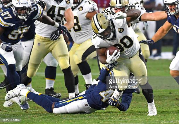 Channing Stribling of the Los Angeles Chargers stops Boston Scott of the New Orleans Saints after a short gain in the preseason game at StubHub...