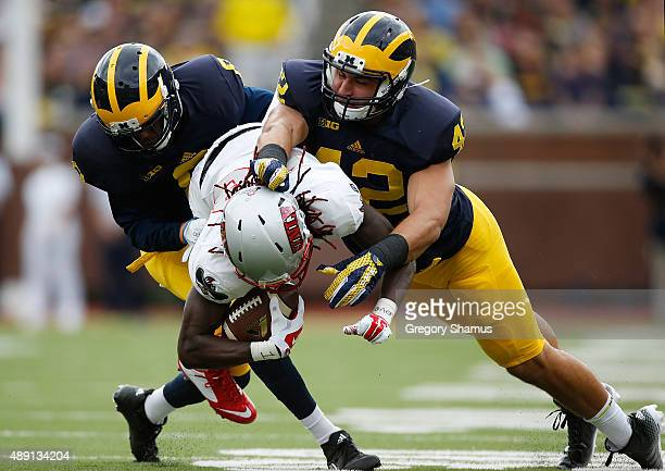 Channing Stribling of the Michigan Wolverines and teammate Ben Gedeon tackle Devonte Boyd of the UNLV Rebels on September 19 2015 at Michigan Stadium...