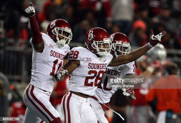 Chanse Sylvie celebrates with Steven Parker and Parnell Motley of the Oklahoma Sooners during the second half against the Ohio State Buckeyes at Ohio...