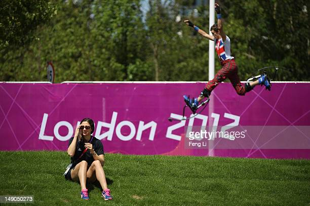 Chantal Brunner of New Zealand Olympic Delegation sits on the grass as a member of the National Youth Theatre of Great Britain practices before a...