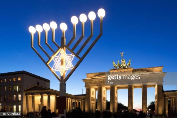 chanukka lights with brandenburg gate at blue hour (berlin, germany) - menorah bildbanksfoton och bilder