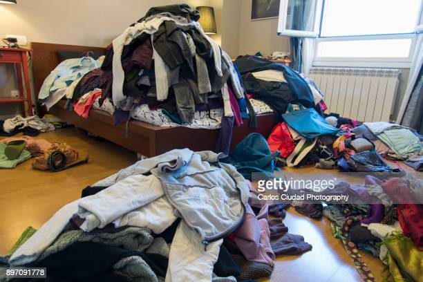 Chaotic room with piles of clothes and other objects thrown around