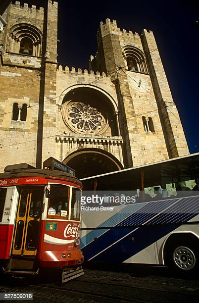 A chaotic scene on the streets of the Portuguese capital as an old tram clashes with a modern tourist coach below the towering Se Cathedral in...