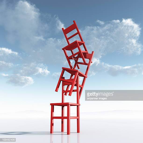 a chaotic stack or pile of red chairs - stability stock pictures, royalty-free photos & images