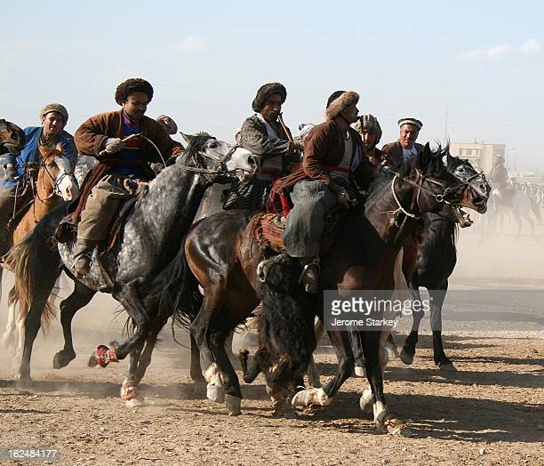 Chapandaz leans over his horse to grab the carcass of a headless, hoofless calf, while the other riders give chase, at a Friday game outside Mazar-e...