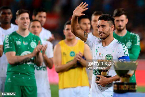 TOPSHOT Chapecoense's defender Alan Ruschel waves to Barcelona players as he holds the second place trophy after the 52nd Joan Gamper Trophy friendly...