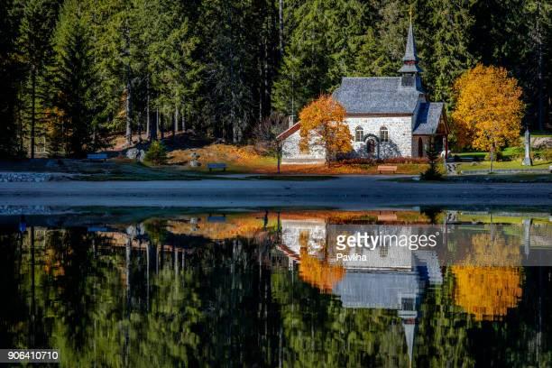 chapelle et et forêt d'automne se reflète dans l'eau du lac de braies, dolomite alps, italie - saint sacrement photos et images de collection