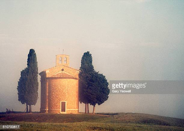 Chapel by Cypress Trees on a hillside in mist