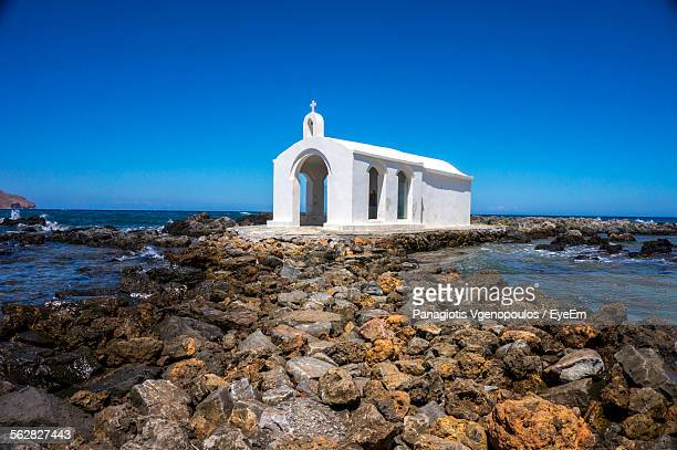 chapel in front of sea against clear blue sky - vgenopoulos stock pictures, royalty-free photos & images