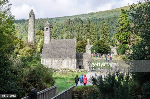 chapel of the monastery of glendalough during day of autumn - irish round tower stock photos and pictures
