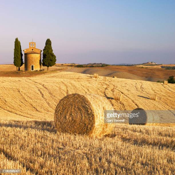 chapel of vitaleta with hay bales in tuscany - capella di vitaleta stock pictures, royalty-free photos & images