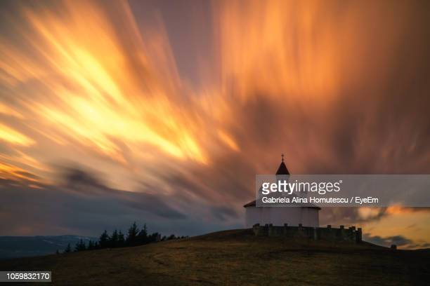 chapel on hill against sky during sunset - gabriela stock pictures, royalty-free photos & images
