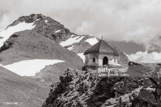 Chapel On Snowcapped Mountain Against Cloudy Sky