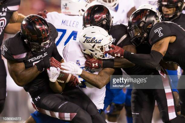 Chapelle Russell, Sam Franklin, and Shaun Bradley of the Temple Owls tackle Shamari Brooks of the Tulsa Golden Hurricane in the first quarter at...