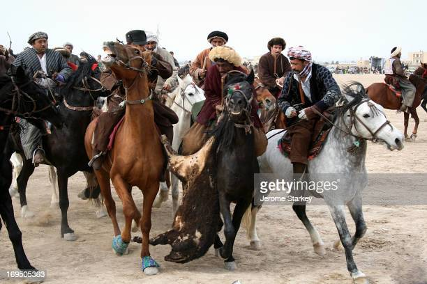 Chapendaz, or professional Buzkashi player, cluthces the back leg of a calf carcass, as he tries to ride clear of the scrum, at a Friday game,...