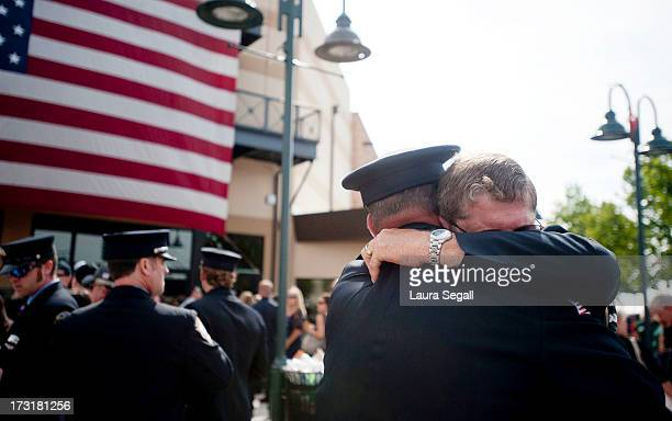 Chaplain Bob Ossler with the Mayer Arizona fire department hugs people at the entrance to a memorial service honoring the 19 firefighters killed in a...