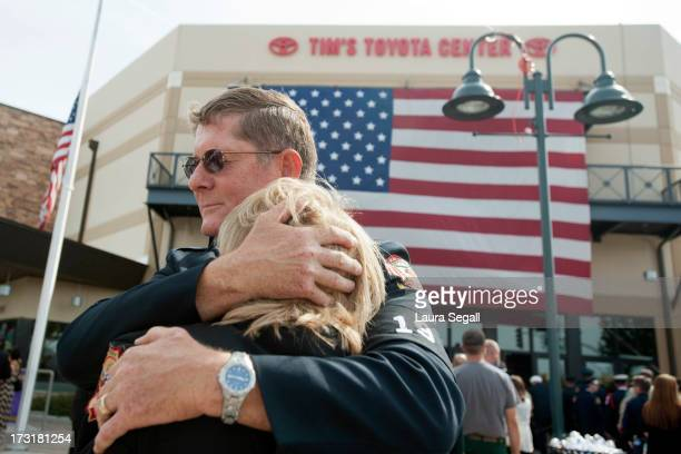 Chaplain Bob Ossler with the Mayer Arizona fire department hugs Mary Dalton assistant chief of the Sun City West Fire Department at the entrance to a...