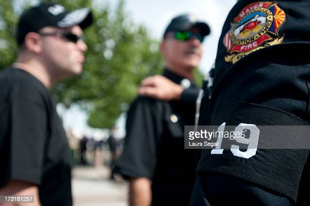 Chaplain Bob Ossler with the Mayer Arizona fire department wears a black arm band with the number 19 at the entrance to a memorial service honoring...