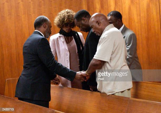 Chaplain Don Hughes prays with Whitney Houston and the rest of her entourage after probation violation hearing for her husband singer Bobby Brown at...