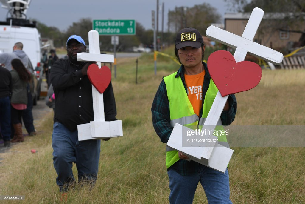 Chaplain Tom Kiyuna (R) helps unload crosses outside the First Baptist Church which was the scene of the mass shooting that killed 26 people in Sutherland Springs, Texas on November 8, 2017. A gunman wearing all black armed with an assault rifle opened fire on a small-town Texas church during Sunday morning services, on November 5, killing 26 people and wounding 20 more in the last mass shooting to shock the United States. /