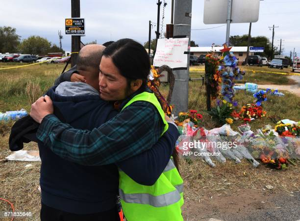 Chaplain Tom Kiyuna hugs Jose Zarman and his son Jaden beside a memorial outside the First Baptist Church which was the scene of the mass shooting...