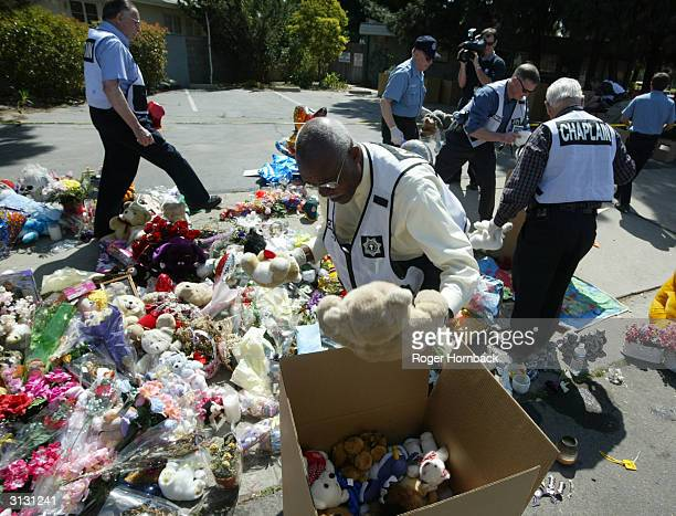 Chaplains from the Fresno City Police Department gather items from a memorial in front of Marcus Wesson's house March 25 2004 in Fresno California...