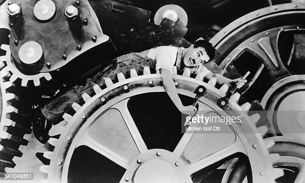Chaplin Charlie Actor film director Great Britain *16041889 Scene from the movie 'Modern Times' Chaplin on the cog wheel Directed by Charles Chaplin...