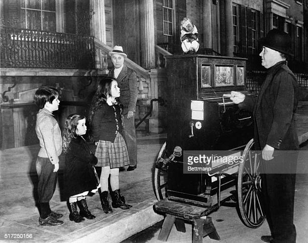 Chaplin Company New York Veteran movie star Charlie Chaplin is momentarily upstaged by three cute children watching an organ grinder in this scene...