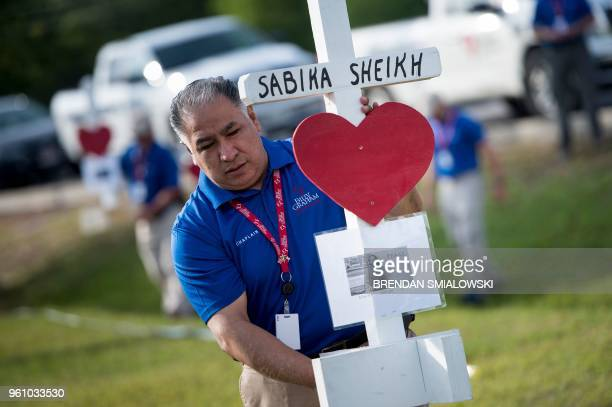 A chaplin with Billy Graham's ministry carries a cross for Sabika Sheikh while delivering the memorials made by Greg Zanis for the victims of the...