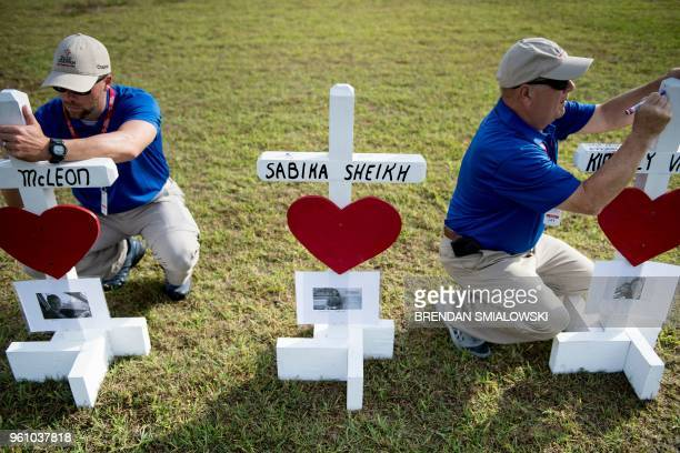 Chaplins with Billy Graham's ministry sign crosses made by Greg Zanis for the victims of the Santa Fe High School shooting at the high school on May...
