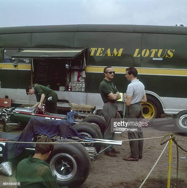 Chapman and Clark outside the Lotus team bus, French Grand Prix, Clermont-Ferrand, France, 1965. Colin Chapman is wearing sunglasses and listening to...