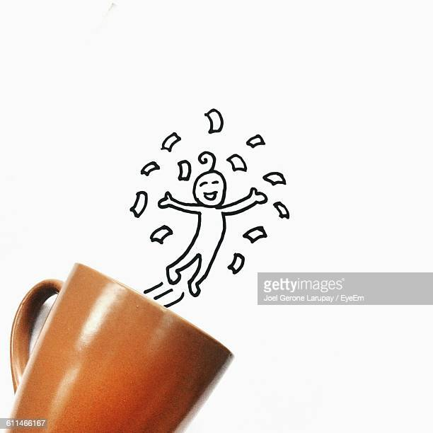 Character Jumping Out Of Coffee Cup Against White Paper