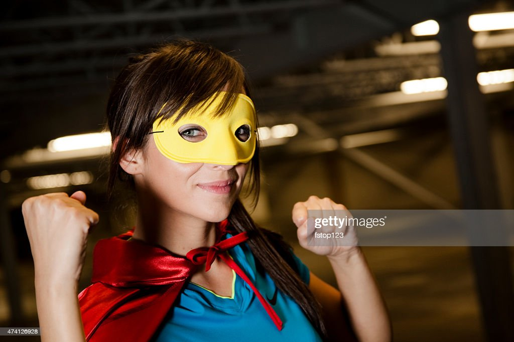 Character: Young adult woman in hero costume. Red cape, mask. : Stock Photo