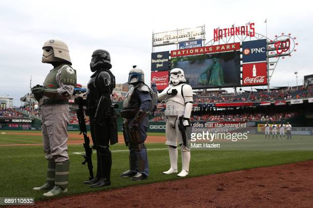 Characters from the Star Wars franchise stand for the playing of the national anthem during Star Wars Day at Nationals Park prior to a game between...