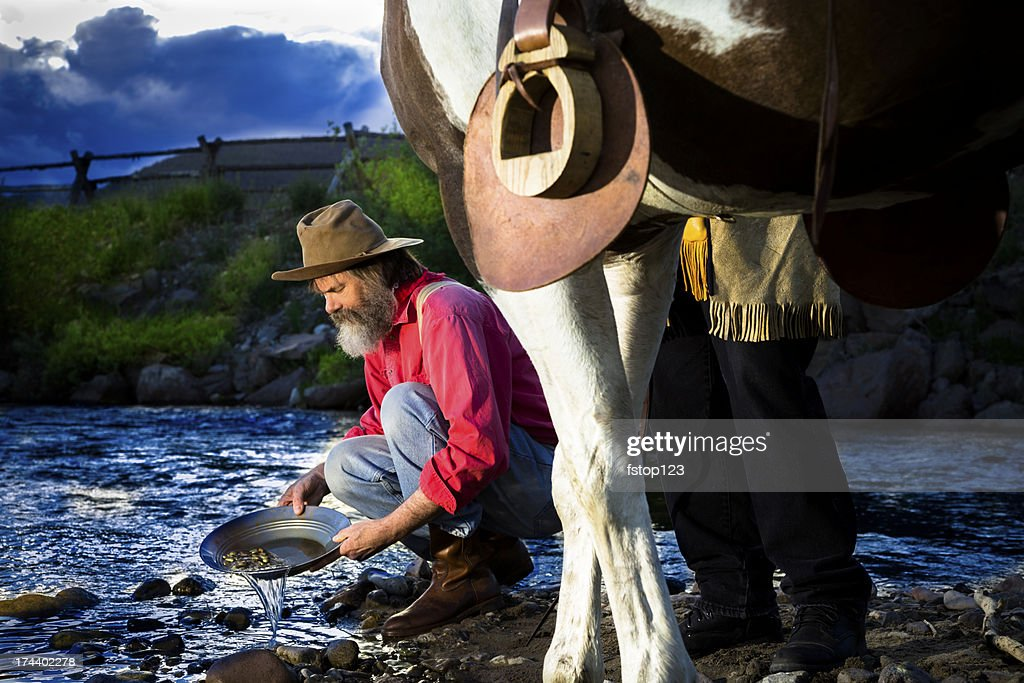 Characters: Gold Prospector pans in stream near mountain. : Stock Photo
