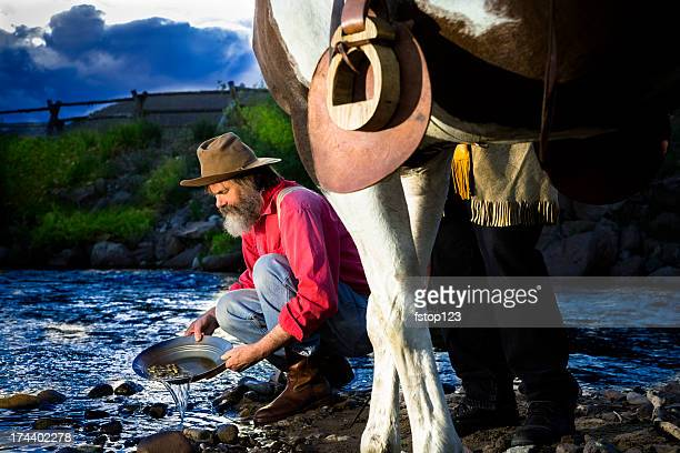 characters: gold prospector pans in stream near mountain. - gold rush stock photos and pictures
