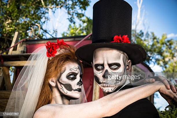 characters: skeleton bride wraps arms around groom. spooky halloween wedding. - freaky couples stock photos and pictures