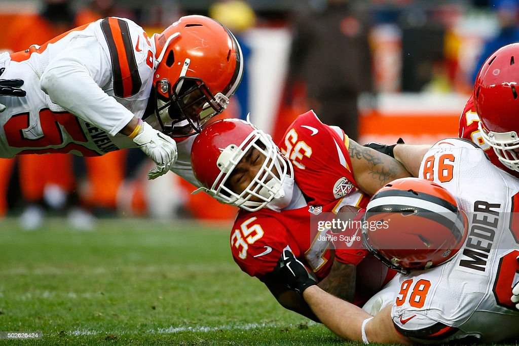 Charcandrick West #35 of the Kansas City Chiefs is tackled by Jamie Meder #98 and Karlos Dansby of the Cleveland Browns at Arrowhead Stadium during the fourth quarter of the game on December 27, 2015 in Kansas City, Missouri.