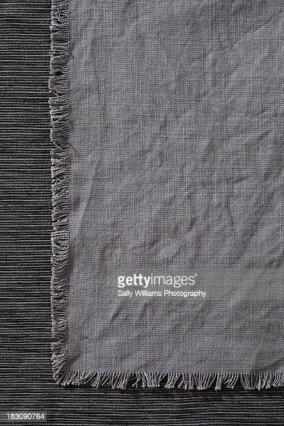 A charcoal grey napkin on a tablecloth