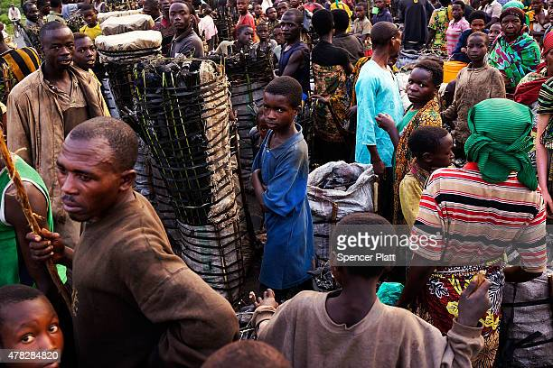 Charcoal workers of a variety of ages wait to sell their loads on June 24, 2015 in Kabezi, Burundi. The men and women often walk most of the night...