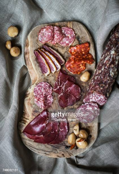 a charcuterie board featuring grisons air-dried beef and salami - charcuterie board stock pictures, royalty-free photos & images