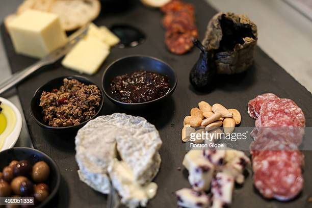 A charcuterie board of miscellaneous meats fruits nuts and cheeses sit on the counter at the Olive Connection in Brookline Mass Sept 16 2015