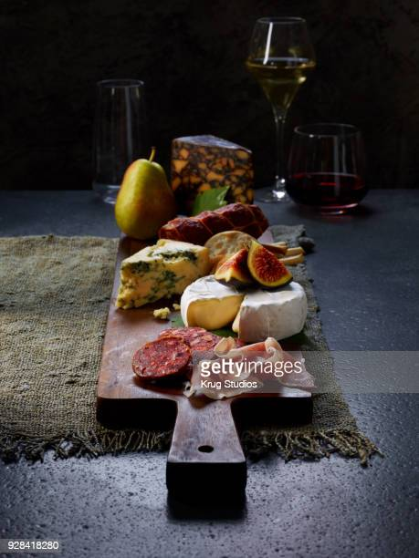 charcuterie board with cheese, meat and fruits - charcuteria fotografías e imágenes de stock
