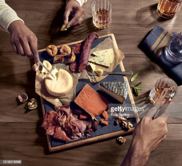 charcuterie board with meats, cheeses, nuts and whisky - charcuteria fotografías e imágenes de stock