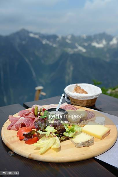 Charcuterie platter and glass of white wine ona table overlooking dramatic mountain view